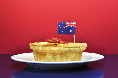 tucker: Australia Day January 26, celebrate with traditional Aussie tucker food such as meat pie with tomato sauce, with an Australian flag Stock Photo