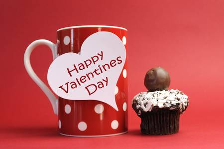 valentine day cup of coffee:  Happy Valentines Day  messages on red polka dot mug with chocolate cupcake against a red background for a bright, fun and cheerful Valentines Day  Stock Photo