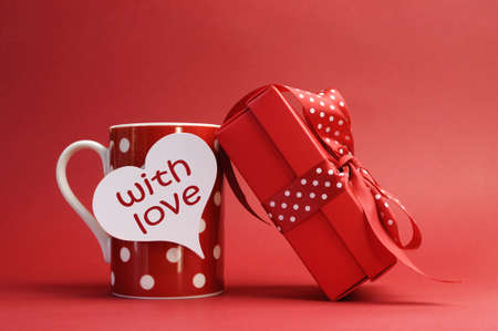 With love  message on red polka dot mug and red gift with polka dot ribbon bow against a red background for a bright, fun and cheerful Valentines Day or special gift of love  photo