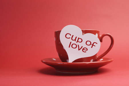 Cup of love message on red polka dot cup and saucer against a red background for a bright, fun and cheerful Valentines Day or to say, I Love You  Stock Photo - 17746500