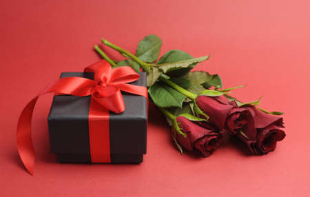 Happy Valentines Day black box with red ribbon gift and red rose, against a red background or to say, I Love You  photo