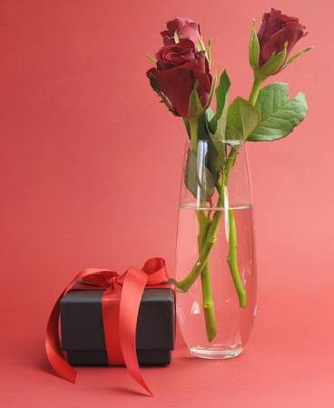 Happy Valentines Day black box with red ribbon gift and red rose, against a red background - or to say, I Love You  photo