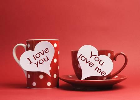te amo: San Valentín Te Amo y Te Amo Me mensajes escritos en carteles etiqueta del corazón en la taza roja de lunares, y la copa y el plato sobre un fondo rojo Foto de archivo