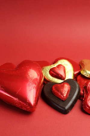 cioccolato natale: Rosso e oro avvolto cioccolatini su uno sfondo rosso per San Valentino o dire ti amo, con copia spazio