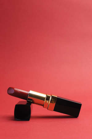 femininity: Iconic symbol of femininity, a luxury red lipstick against a red background, vertical with copy space  Stock Photo
