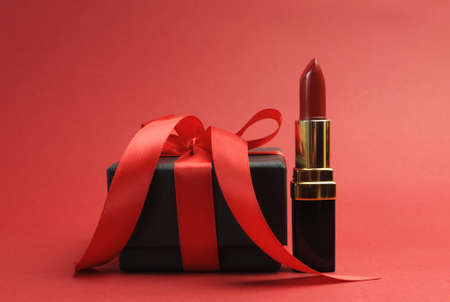 Beautiful luxury red lipstick with black box gift against a red background  photo