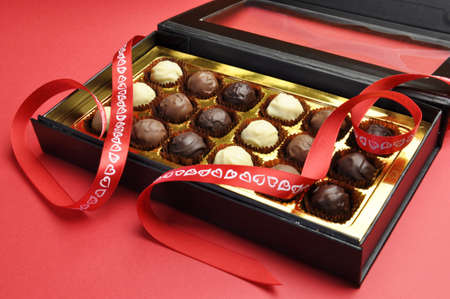 Beautiful black and gold box of delicious white, milk and dark chocolates in a black and gold box with romantic red heart ribbon on a red background, for Valentine or saying, I Love You  Stock Photo