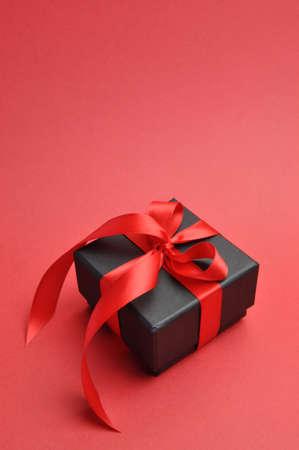 ruban noir: Beau cadeau de Valentine boîte noire présente à l'arc ruban rouge sur un fond rouge vertical avec copie espace pour votre texte ici