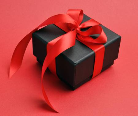 Beautiful Valentine black box gift present with red ribbon bow on a red background  Stock Photo - 17746488