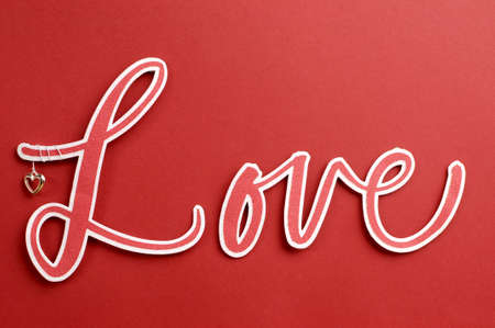 Love spelt in letters with cute heart against a red background, for Valentine or special greeting  Stock Photo - 17746741