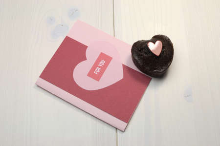 Love theme handmade gift card with For You greeting and mini chocolate muffin cup cake treat on shabby chic table  photo