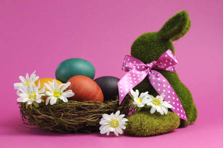 Pink theme Happy Easter scene still life with grass bunny rabbit with rainbow color eggs in a nest with white daisies  photo