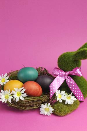 Pink theme Happy Easter scene still life with grass bunny rabbit with rainbow color eggs in a nest with white daisies  Vertical with copy space  photo