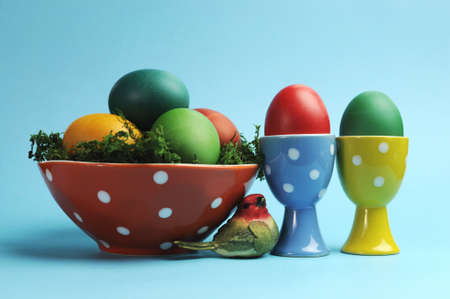 Bright and cheerful Happy Easter still life with rainbow color eggs in orange polka dot bowl and egg cups against a blue background  photo