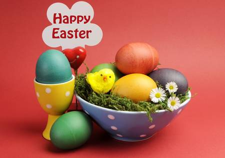 Bright and cheerful Happy Easter still life with rainbow color eggs in blue polka dot bowl against a red background, with egg cups and  happy Easter  sign Stock Photo - 17746796