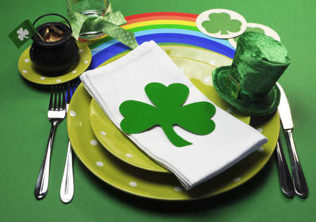 St Patricks Day party table dinner setting with rainbow, leprechaun hat and shamrocks photo