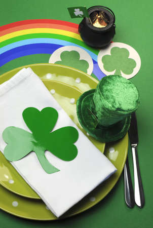 St Patricks Day party table dinner setting with rainbow, leprechaun hat and shamrocks - vertical  photo