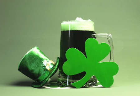 Happy St Patricks Day with glass stein of green beer, leprechaun hat and shamrock  photo