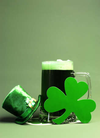 stein: Happy St Patricks Day with glass stein of green beer, leprechaun hat and shamrock - vertical with copy space for your text here