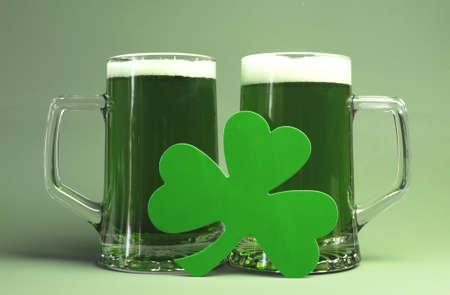 Happy St Patrick s Day two glass steins of green beer and shamrock  Stock Photo