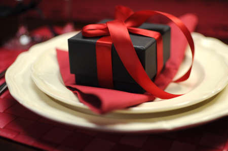 Closeup with bokeh of black box present gift with red ribbon on romantic Valentine table setting Stock Photo - 17759095