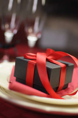 Closeup with bokeh of black box present gift with red ribbon on romantic Valentine table setting Stock Photo - 17759188