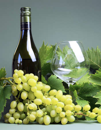 sultana: Bottle of white wine, wine glass with a large bunch of sultana grapes and grape vine leaves - vertical  Stock Photo