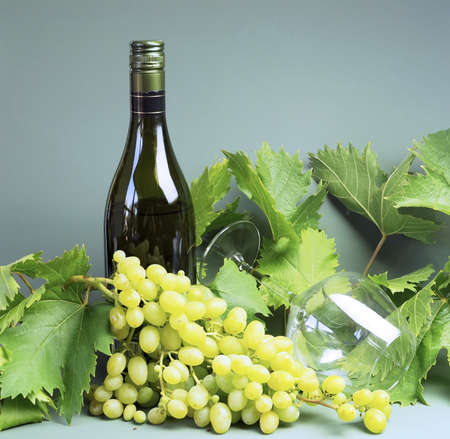 sultana: Bottle of white wine, wine glass with a large bunch of sultana grapes and grape vine leaves  Stock Photo