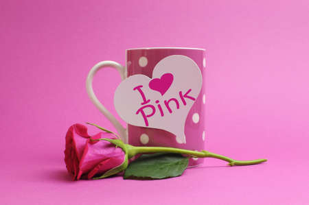 I love  heart  pink  message written on a white heart sign on a pink polka dot coffee mug with a pink rose bud against a pink background  photo