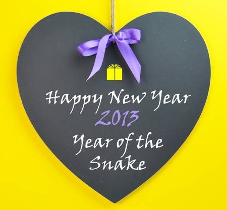 Happy New Year, 2013 the Year of the Snake in Chinese astrology, message on a blackboard with purple ribbon on a yellow background. photo
