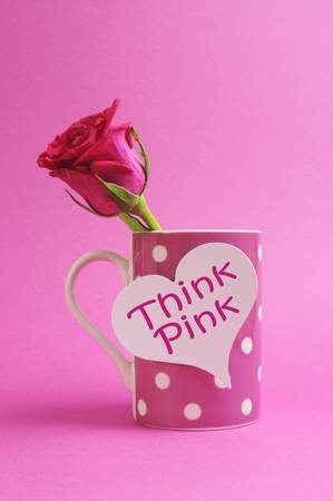 Pink polka dot mug with heart sign, Think Pink, with pink rose bud against a pink background  photo