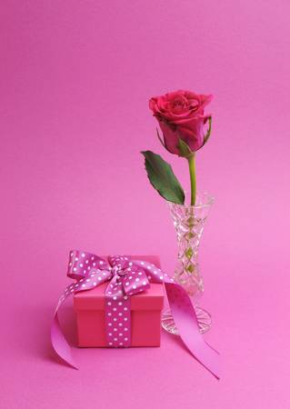 Pretty pink gift with polka dot pink ribbon and pink rose against a pink background  photo