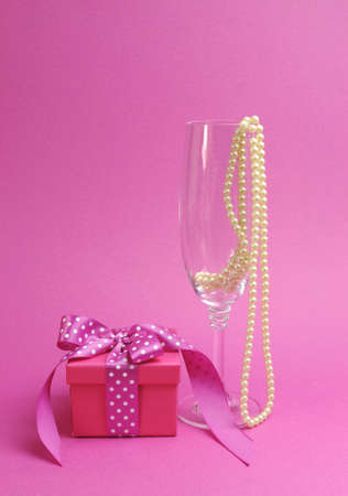Pretty pink and feminine gift with polka dot pink ribbon and a champagne glass with pearls against a pink background  Vertical portrait orientation  photo
