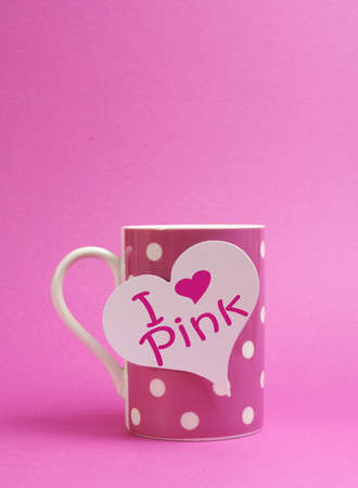 Pink polka dot mug with heart sign, I Heart  love  Pink, against a pink background  Vertical portrait orientation, with copy space for your text here  photo