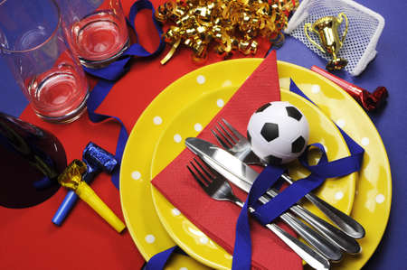 Soccer football celebration party table settings in red, yellow and blue team colors