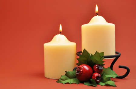 lit candle: A pair of two creamy white lit candles with green and red holly decoration against a red orange background set the scene for a stylish Christmas Eve setting