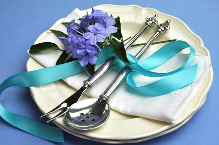 Blue theme table setting with beautiful silver cutlery, plates and serviette napkins for a modern twist on traditional table setting elegance  Stock Photo