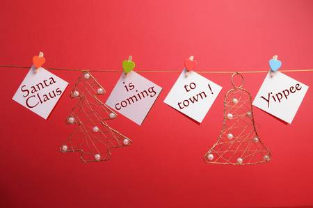 weihnachtsmann lustig: Santas Claus kommt in die Stadt Nachricht geschrieben Coming on hängen Schilder mit Zapfen von Weihnachten Ornament Linie gegen einen festlichen Urlaub rotem Hintergrund Lizenzfreie Bilder