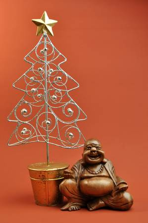 East meets West concept with a Laughing Buddha sitting next to a Christmas Tree ornament, and set against a red orange background