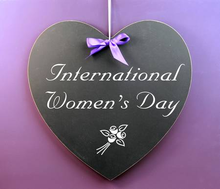womens day: International Women s Day message written on heart shape blackboard sign against a purple background