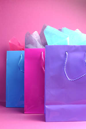 retail therapy: Retail therapy, I love shopping, concept with colorful shopping bags against a pink background, vertical with 3 bags front view