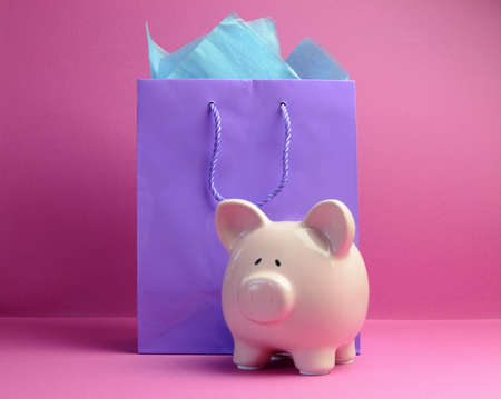 retail therapy: Retail therapy, savings, concept with colorful shopping bags against a pink background, with piggy bank  Stock Photo