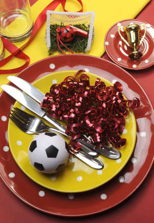 Soccer football celebration party table settings in red and yellow team colors  vertical  photo