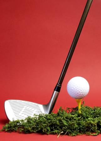 golf stick: Sporting and Leisure pursuit, golf club iron, yellow tee with white golf ball on grass against  a red background, vertical with copy space.