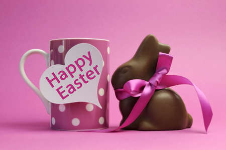 easter message: Happy Easter pink polka dot coffee or tea mug with white heart shape gift tag sign and chocolate bunny with pink ribbon, with Happy Easter message