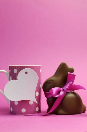 easter message: Happy Easter pink polka dot coffee or tea mug with white heart shape gift tag sign and chocolate bunny with pink ribbon  Vertical, with copy space for your text here  Stock Photo
