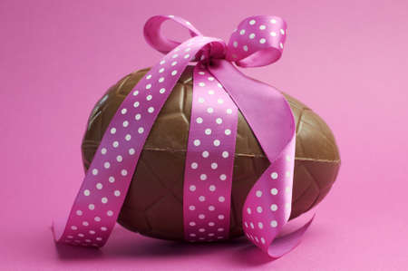 Large Happy Easter chocolate Easter egg with pink polka dot ribbon tied in a bow against a pretty feminine pink background