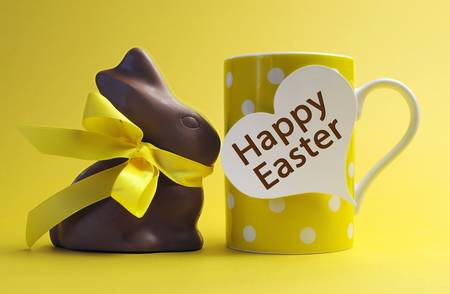 Yellow theme polka dot breakfast coffee mug with chocolate bunny rabbit and heart shape message saying Happy Easter. Stock Photo