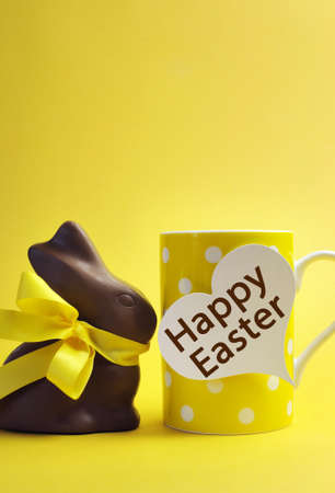 easter sunday: Yellow theme polka dot breakfast coffee mug with chocolate bunny rabbit and heart shape message saying Happy Easter. Vertical with copy space for your text here.