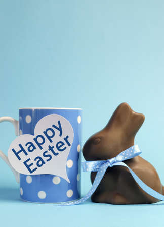 Blue theme polka dot breakfast coffee mug with chocolate bunny rabbit and heart shape message saying Happy Easter. Vertical with copy space for your text here photo